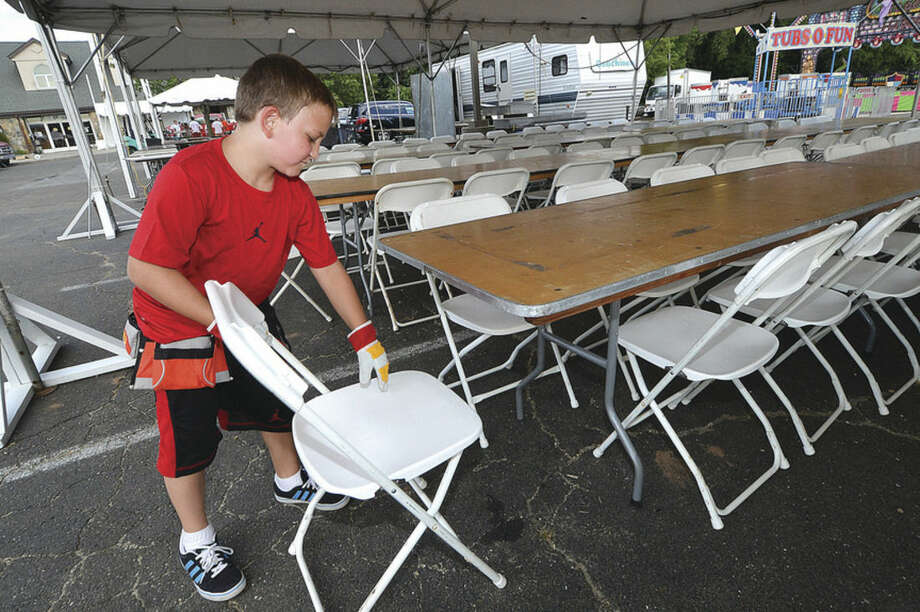 Hour Photo/Alex von Kleydorff 9yr old Anthony Vozzo helps to set up folding chairs for the dining tables for the St Ann feast this weekend