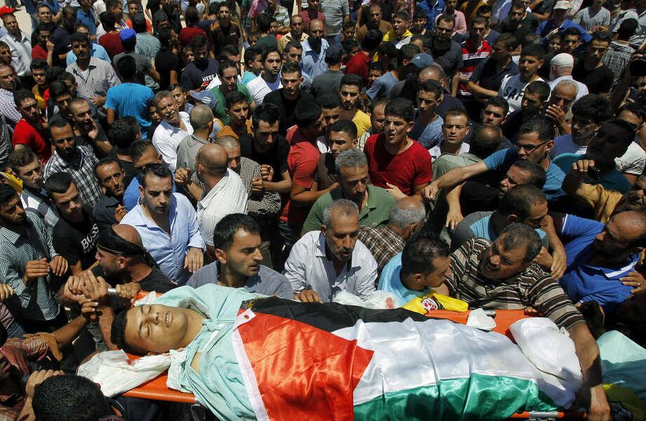 Palestinian mourners carry the body of 21-year-old Mohammed Ahmed Alauna, who was killed in clashes with Israeli troops in the West Bank village of Burqin, near Jenin on Wednesday, July 22, 2015. The Israeli military said its troops were on a routine patrol in the West Bank when they were attacked by a group of Palestinians hurling rocks in their direction. (AP Photo/Mohammed Ballas)