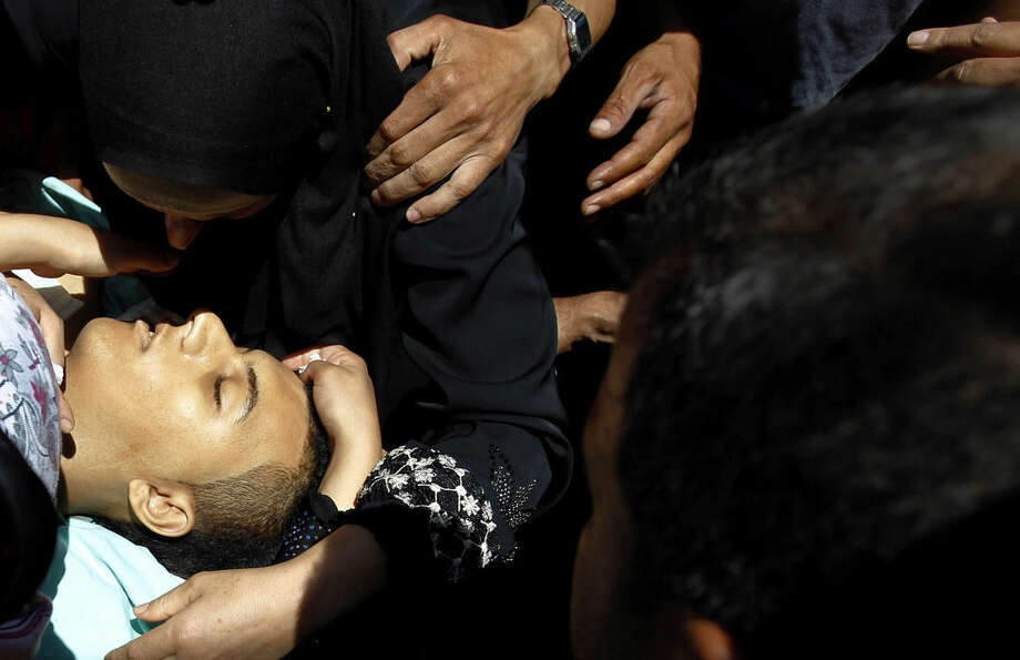 Palestinian mourners stand by the body of 21-year-old Mohammed Ahmed Alauna, who was killed in clashes with Israeli troops in the West Bank village of Burqin, near Jenin on Wednesday, July 22, 2015. The Israeli military said its troops were on a routine patrol in the West Bank when they were attacked by a group of Palestinians hurling rocks in their direction. (AP Photo/Mohammed Ballas)