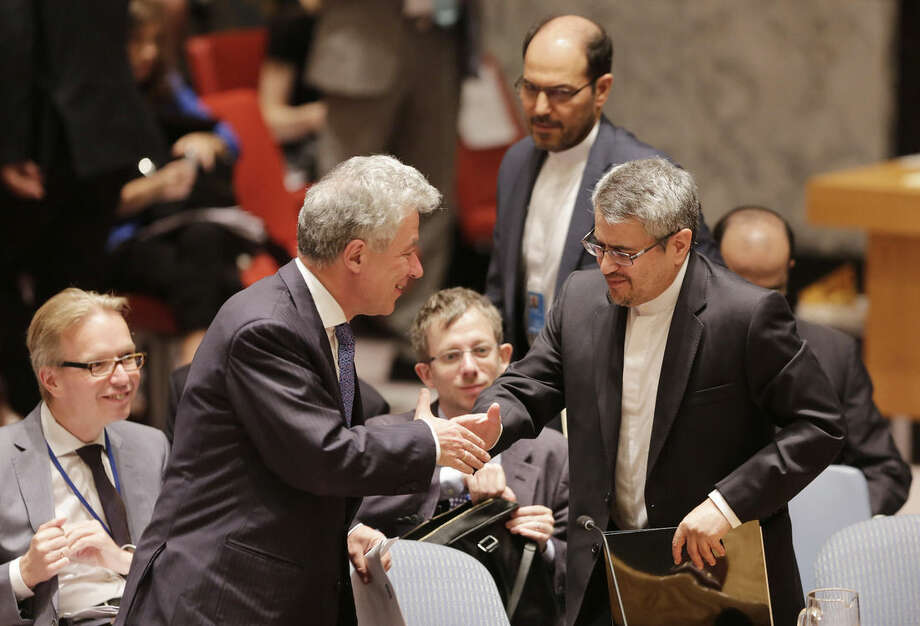 Thomas Mayr-Harting, left, head of the delegation of the European Union to the United Nations, shakes hands with Iran's U.N. Ambassador, Gholamali Khoshroo, at United Nations headquarters, Monday, July 20, 2015. The U.N. Security Council on Monday unanimously endorsed the landmark nuclear deal between Iran and six world powers and authorized a series of measures leading to the end of U.N. sanctions that have hurt Iran's economy. (AP Photo/Mark Lennihan)