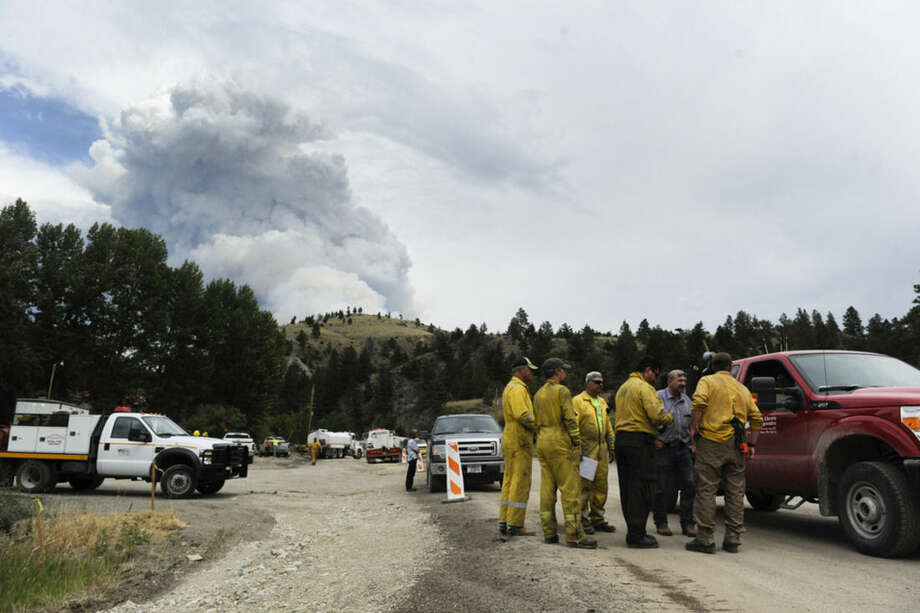 Wildland firefighters chat with Deep Creek landowners as smoke rises from a wildfire near Townsend, Mont., Tuesday, July 21, 2015. The fire has closed a portion of U.S. Highway 12 and led to evacuation orders in the rural area. (Thom Bridge/The Independent Record via AP) MANDATORY CREDIT
