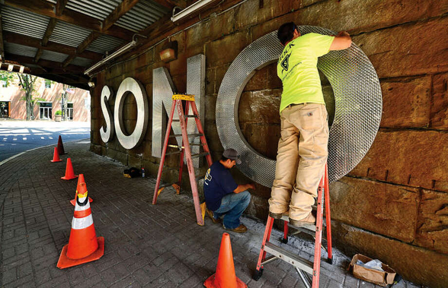 Hour photo / Erik Trautmann Workers with Shock Electrical mount a sign under the railroad bridge on Washington St. Wednesday ahead of the SoNo Arts Festival this summer.