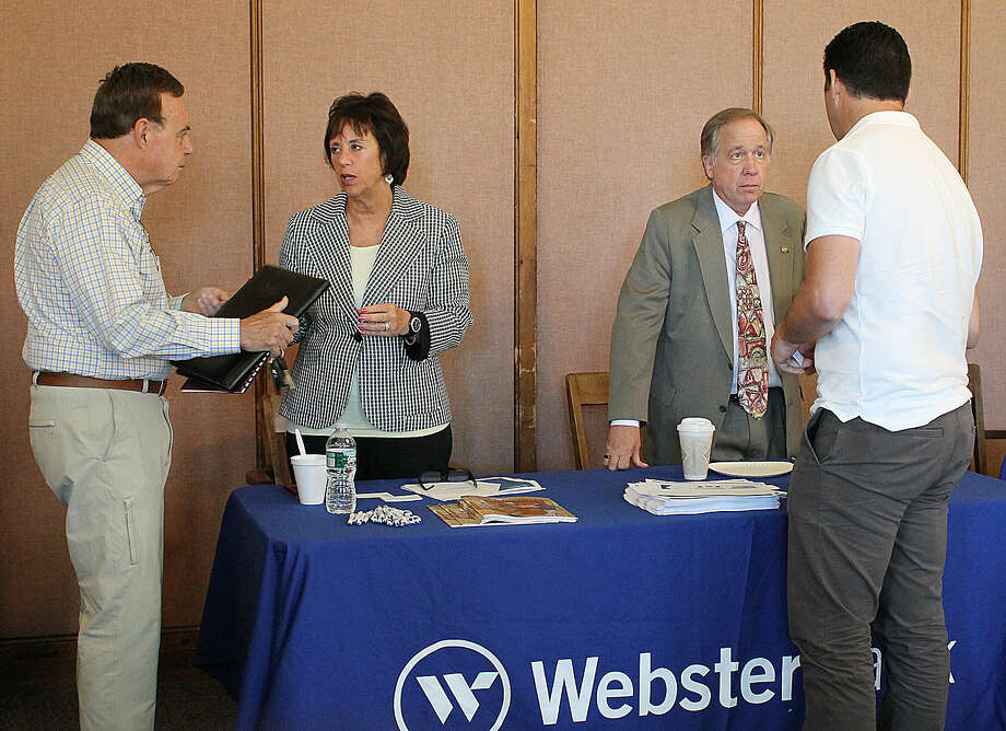 Hour Photo/ Rachel Sawyer Webster Bank representatives talk to visitors at the SBA and AARP CT event Wednesday at Norwalk City Hall.