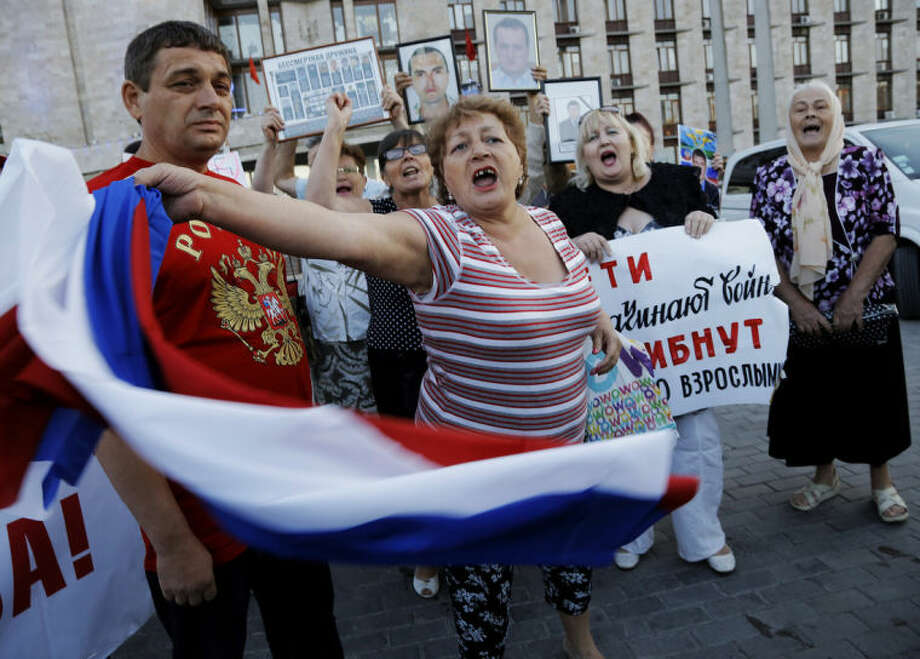 Pro-Russian demonstrators shout slogans in Donetsk, eastern Ukraine, Monday, June 23, 2014. Leaders of the self-proclaimed Donetsk People's Republic and Luhansk People's Republic met Monday with former Ukrainian President Leonid Kuchma, OSCE Ambassador Heidi Tagliavini, and Russian Ambassador in Ukraine Mikhail Zurabov, as insurgents promised Monday to honor a cease-fire declared by the Ukrainian president and engage in more talks to help resolve the conflict.(AP Photo/Dmitry Lovetsky)