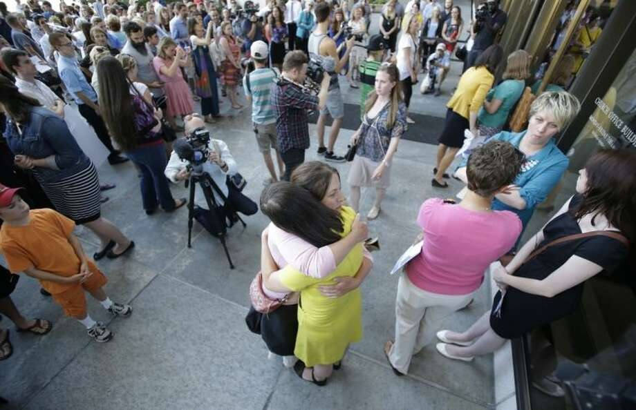 In this Sunday, June 22, 2014, photo, Kate Kelly, the founder of a prominent Mormon women's group, center right, receives a hug from a supporter during a vigil, in Salt Lake City. Kelly could find out Monday if she will be excommunicated from her church. (AP Photo/Rick Bowmer)
