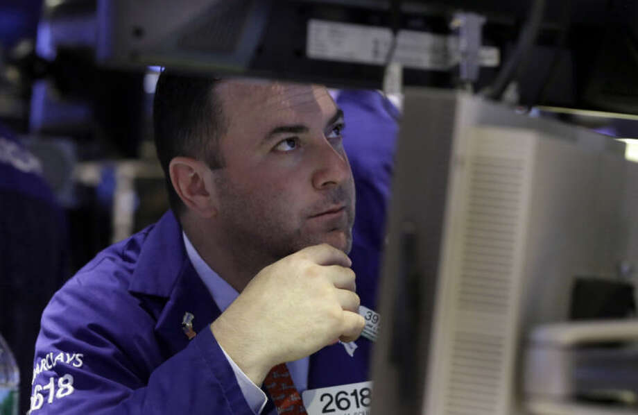 Specialist James Sciulli works at his post on the floor of the New York Stock Exchange Monday, June 23, 2014. Stocks are edging lower in early trading after indexed closed last week at record highs. (AP Photo/Richard Drew)