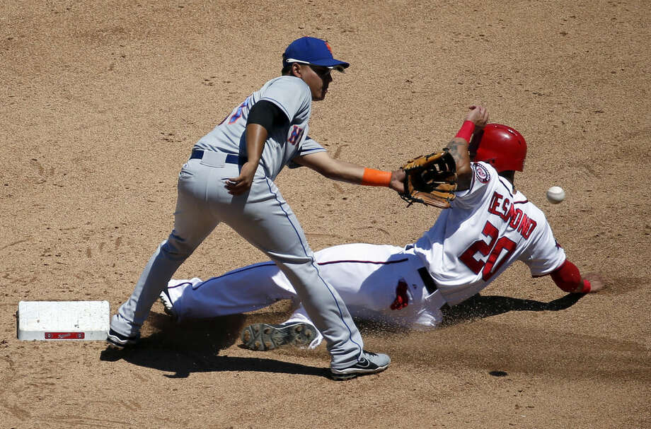 New York Mets shortstop Ruben Tejada (11) waits for the throw as Washington Nationals' Ian Desmond (20) safely steals second base during the fourth inning of a baseball game at Nationals Park, Wednesday, July 22, 2015, in Washington. (AP Photo/Alex Brandon)