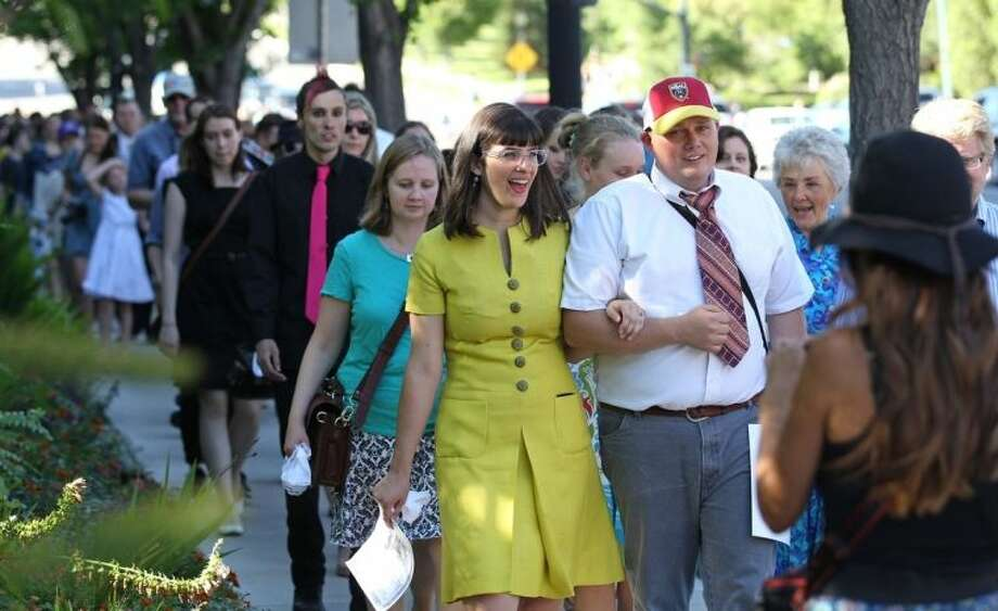 Kate Kelly, center, walks with supporters to the Church Office Building of the Church of Jesus Christ of Latter-day Saints during a vigil Sunday, June 22, 2014, in Salt Lake City. While Kate Kelly's former church leaders meet in Virginia on Sunday night to decide if she'll be ousted from her church, the founder of a prominent Mormon women's group will hold a vigil in Salt Lake City along with hundreds of her supporters. The leader of Ordain Women is accused of apostasy, defined as repeated and public advocacy of positions that oppose church teachings. (AP Photo/Rick Bowmer)