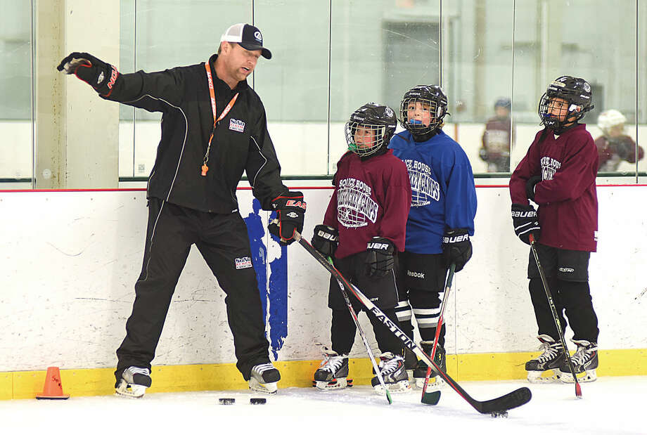 Hour photo/John Nash - Former Trinity Catholic and Darien High hockey coach Chris Gerwig, left, has been hired by the Connecticut Oilers junior hockey organization.