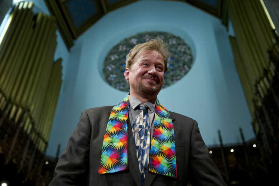 United Methodist pastor Frank Schaefer smiles after a news conference Tuesday, June 24, 2014, at First United Methodist Church of Germantown in Philadelphia. Schaefer, who presided over his son's same-sex wedding ceremony and vowed to perform other gay marriages if asked, can return to the pulpit after a United Methodist Church appeals panel on Tuesday overturned a decision to defrock him. (AP Photo/Matt Rourke)