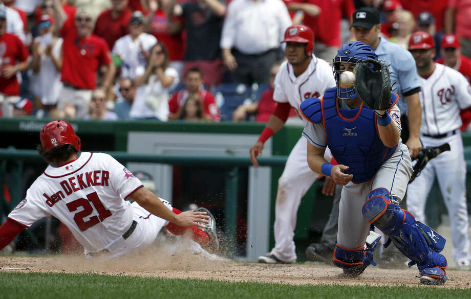 Washington Nationals' Matt den Dekker (21) slides safely home on a Michael Taylor single, as New York Mets catcher Kevin Plawecki (22) waits for the throw during the eighth inning of a baseball game at Nationals Park, Wednesday, July 22, 2015, in Washington. The Nationals won 3-2. (AP Photo/Alex Brandon)