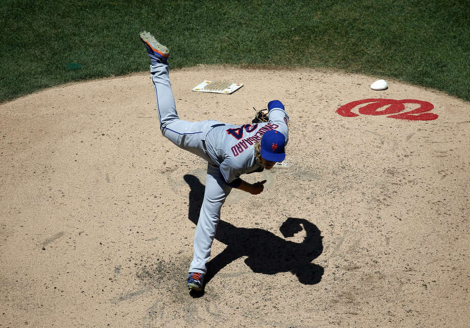 New York Mets starting pitcher Noah Syndergaard follows through on a pitch during the fifth inning of a baseball game against the Washington Nationals at Nationals Park, Wednesday, July 22, 2015, in Washington. (AP Photo/Alex Brandon)