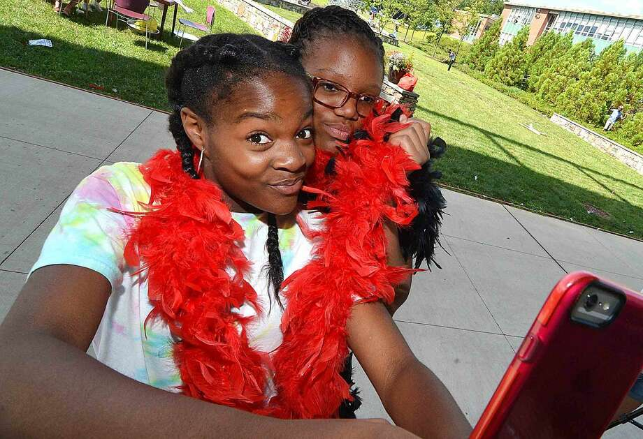 Hour Photo/Alex von Kleydorff Siera and Zariah take a selfie wwearing feather boa's during a Roaring 20's party at NCC hosted for the afterschool program by Family and Childrens Agency