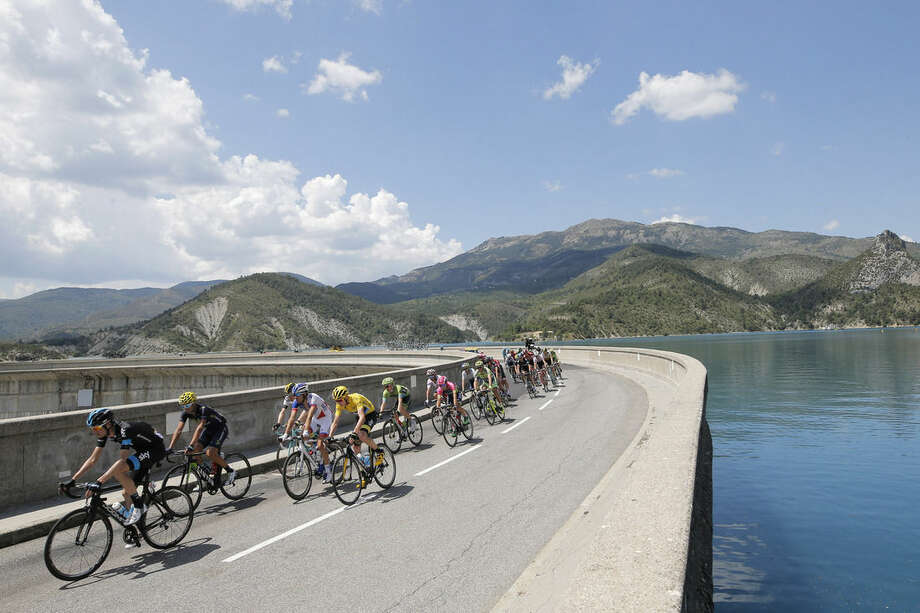The pack with Britain's Chris Froome, wearing the overall leader's yellow jersey, rides during the seventeenth stage of the Tour de France cycling race over 161 kilometers (100 miles) with start in Digne-les-Bains and finish in Pra Loup, France, Wednesday, July 22, 2015. (AP Photo/Laurent Cipriani)