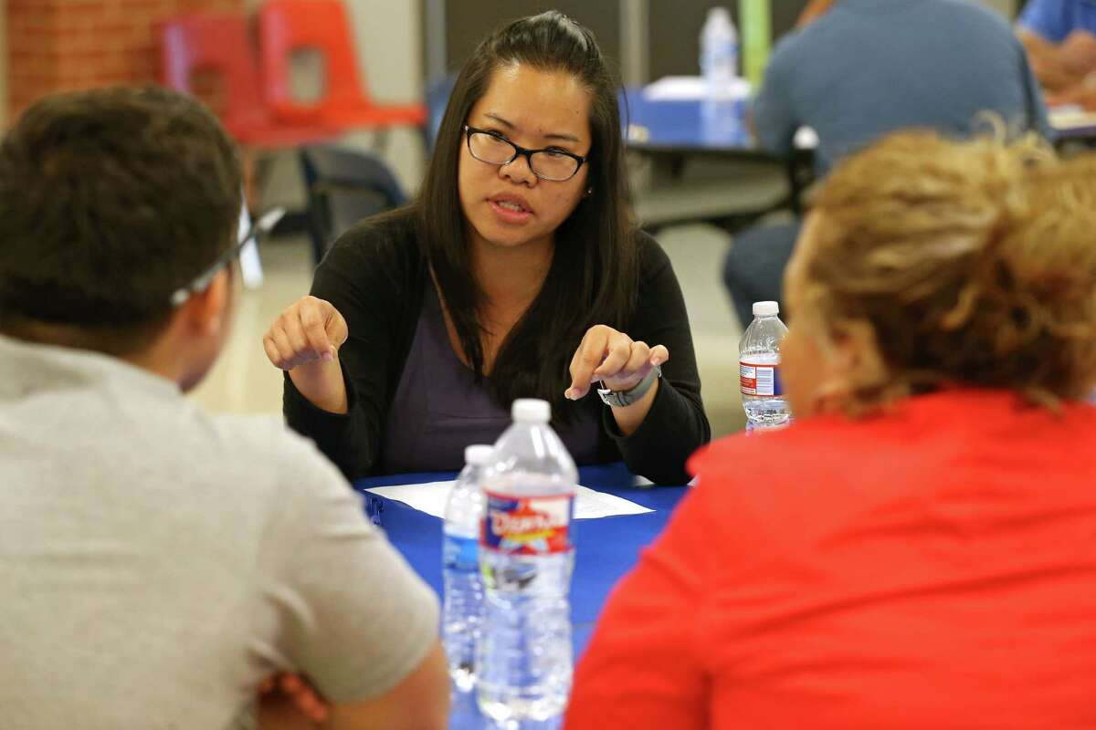 """Mentor Hsiang Yee Lai (center) talks with Edison High School junior Livan Hernandez (left) and his mother Maria Hernandez during the San Antonio Independent School District """"Students on the Rise"""" program held Thursday May 28, 2016 at Edison High School."""