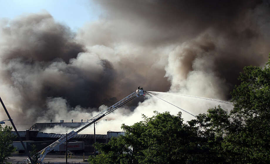 Firefighters battle a multiple-alarm fire at a large warehouse in North Brunswick, N.J., Wednesday, July 22, 2015. The fire in central New Jersey that was fueled by plastics, autos and household goods sent plumes of black smoke into the air that were visible from space. (Mark R. Sullivan/Home News Tribune via AP)