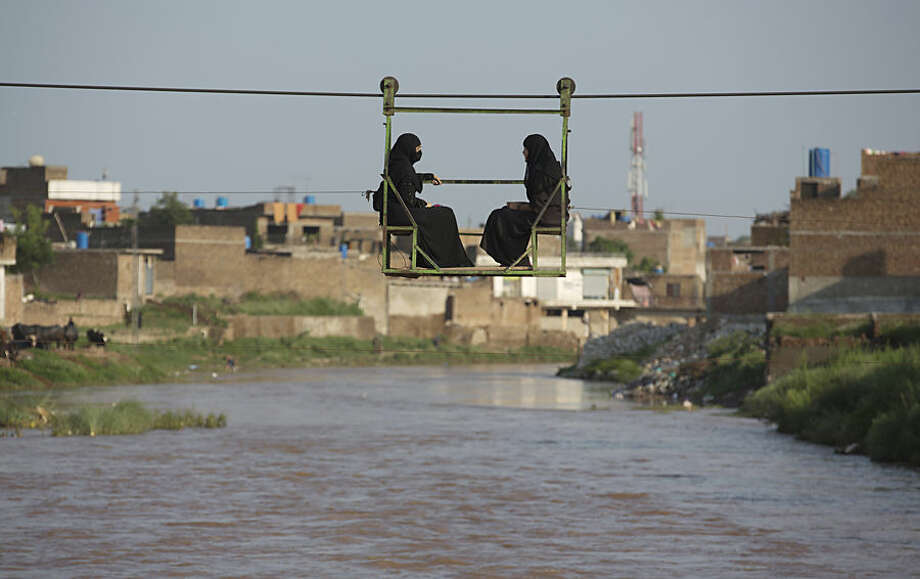 Pakistani women sit in a trolley crossing a stream flooded due to heavy rains in Rawalpindi, Pakistan, Wednesday, July 22, 2015. Pakistan's military deployed helicopters and boats Wednesday to evacuate flood victims from the country's north, where monsoon rains and flash floods washed away several villages this week. (AP Photo/Mohammad Sajjad)