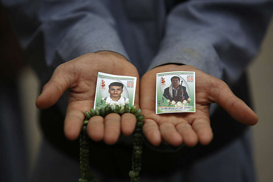 A Shiite rebel known as a Houthi displays pictures of his relatives, who were killed in a recent a car bomb attack, during their funeral in Sanaa, Yemen, Wednesday, July 22, 2015. (AP Photo/Hani Mohammed)