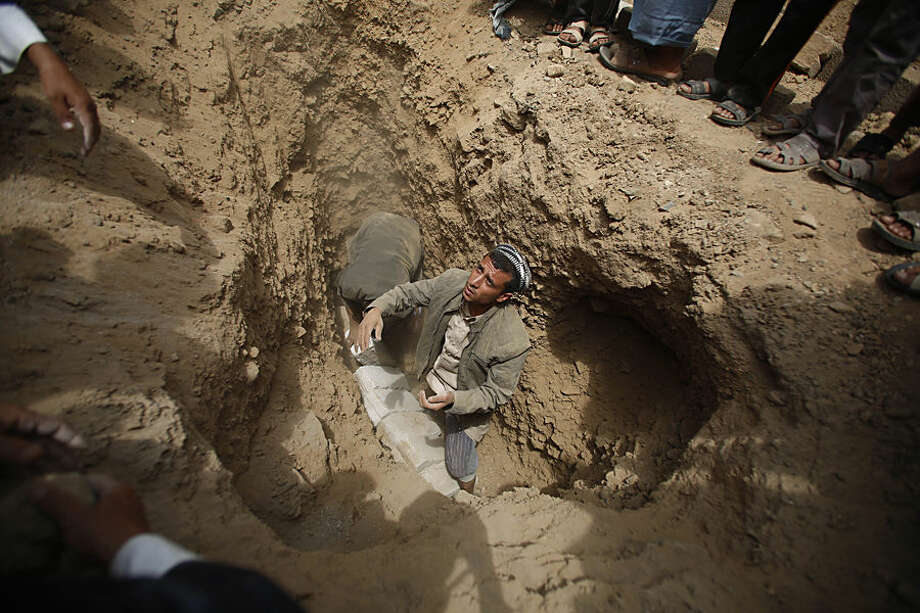 Shiite rebels known as Houthis bury a fellow Houthi, who was killed in a recent a car bomb attack, during his funeral in Sanaa, Yemen, Wednesday, July 22, 2015. (AP Photo/Hani Mohammed)