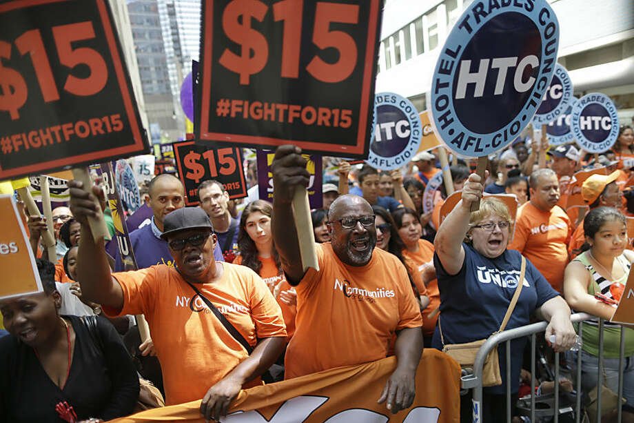Activists cheer during a rally after the New York Wage Board endorsed a proposal to set a $15 minimum wage for workers at fast-food restaurants with 30 or more locations, Wednesday, July 22, 2015 in New York. The increase would be phased in over three years in New York City and over six years elsewhere. (AP Photo/Mary Altaffer)