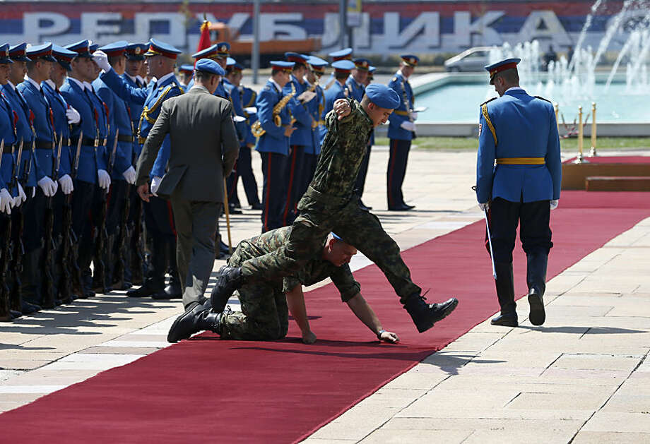 Serbian army soldiers prepare the red carpet before the welcoming ceremony for Bosnia's three-member presidency in Belgrade, Serbia, Wednesday, July 22, 2015. Bosnia's three-member presidency visits Belgrade following recent tensions over the 20th anniversary of the Srebrenica massacre of Muslims by Serbs. (AP Photo/Darko Vojinovic)