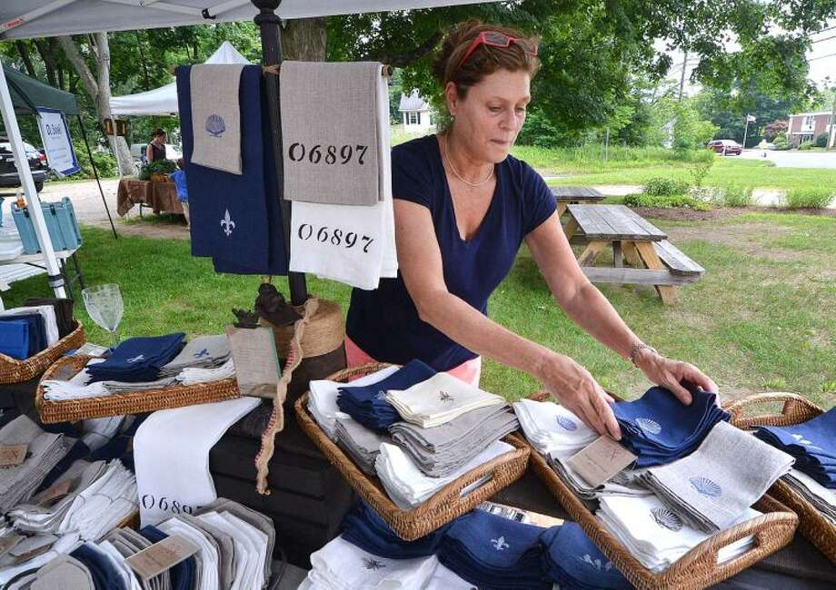 Artist Anita Sobelson straightens some of her hand made unique linen napkins at her Anita Designs table at Wilton Farmers Market.