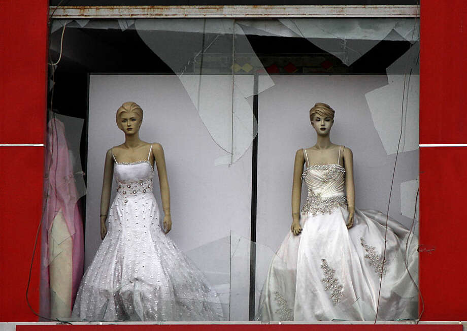 A bridal boutique damaged a day after a car bombing hit the eastern neighborhood of New Baghdad, Iraq, Wednesday, July 22, 2015. On late Tuesday a car bomb detonated in front of a busy clothing store, killing and wounding civilians, officials said. (AP Photo/ Khalid Mohammed)