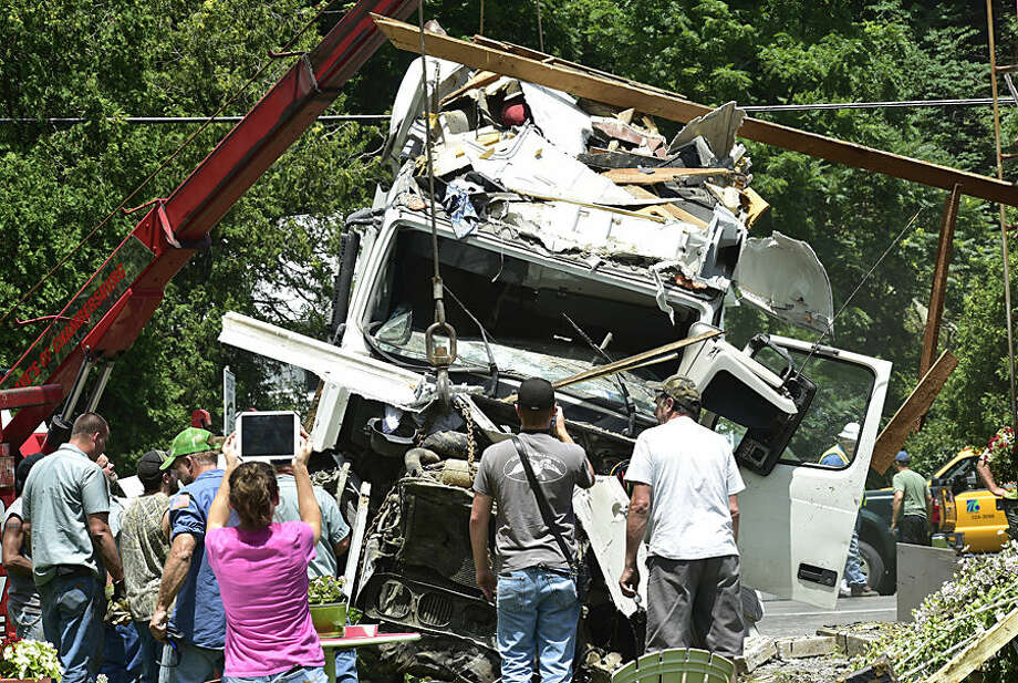 People photograph a tractor-trailer after it was removed from a home following a crash on Buchanan Trail West, Wednesday, July 22, 2015, near Mercersburg, Pa. The driver lost control of his rig and struck the house. (Markell DeLoatch/Public Opinion via AP)