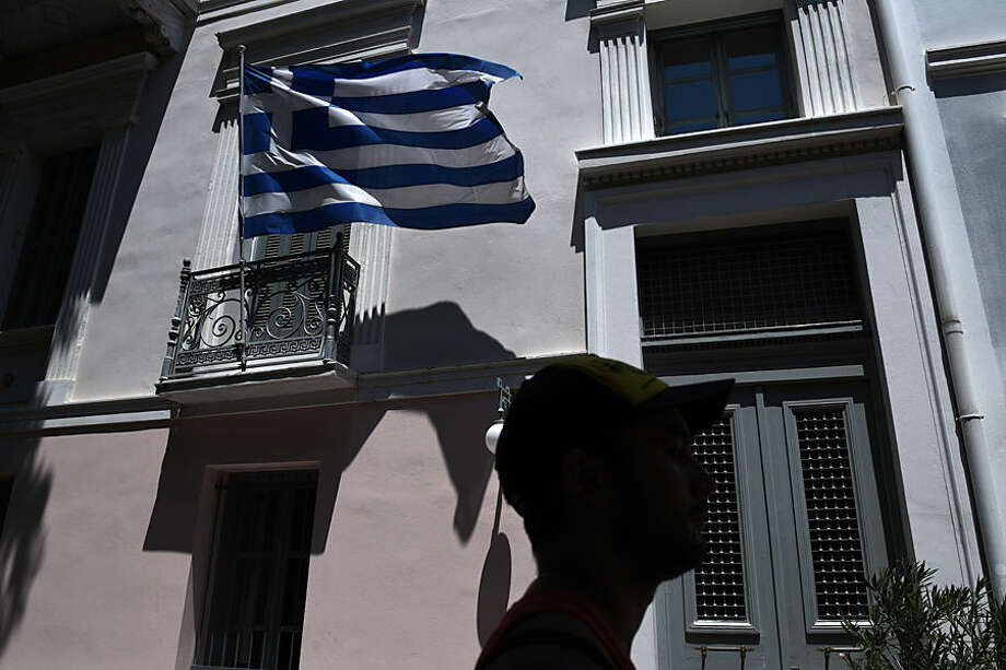 A pedestrian passes a Greek flag in Athens, Wednesday, July 22, 2015. Greek lawmakers began another emergency debate Wednesday on further economic reforms demanded by international creditors in return for a new bailout, a vote that could threaten the survival of the coalition government and trigger fresh fears over the country's future in the euro. (AP Photo/Giannis Papanikos)