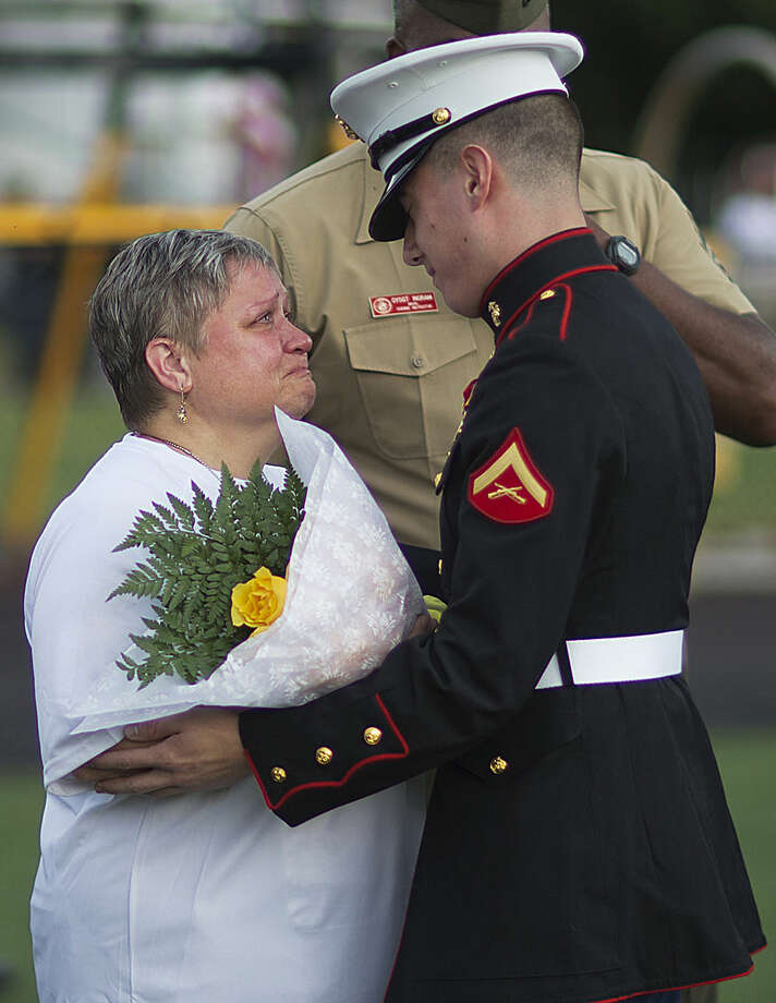 """Cathy Wells, left, the mother of Lance Cpl. Squire Wells, known as """"Skip,"""" is embraced by Lance Cpl. Kurt Bright, one of Wells' best friends upon arriving for a memorial service for her son at Sprayberry High School where he attended, Tuesday, July 21, 2015, in Marietta, Ga. Crowds gathered at the suburban Atlanta high school to remember the Marine who was fatally shot in an attack on military facilities in Chattanooga, Tenn. (AP Photo/David Goldman)"""