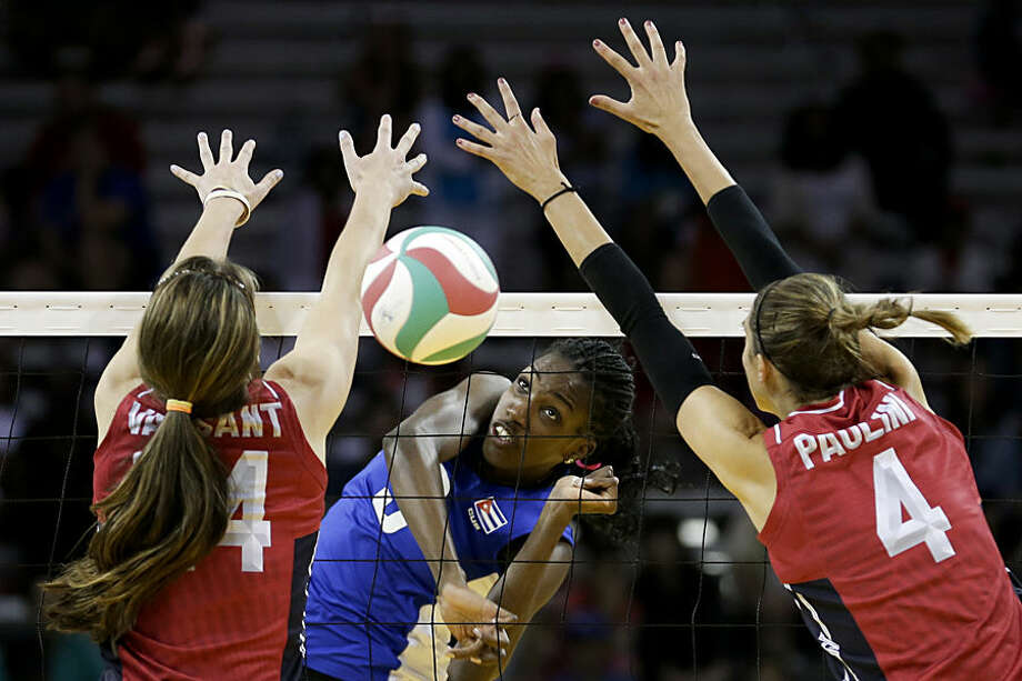 Cuba's Alena Rojas, center, hits over the net as the United States' Krista Vansant, left, and Lauren Paolini defend in their women's quarterfinal volleyball match in the Pan Am Games in Toronto Wednesday, July 22, 2015. The United States won, 3-1. (AP Photo/Gregory Bull)