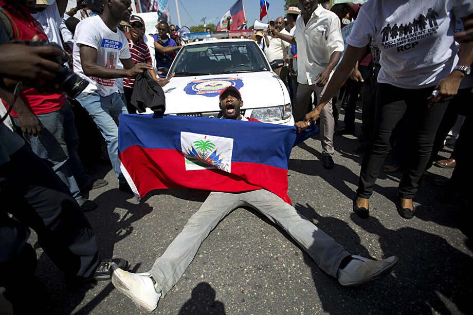 """A demonstrator holding a Haitian flag shouts, """"No racism"""" as he blocks a police car during a march to the prime minister's office to protest the Dominican Republic's deportation of Haitians, in Port-au-Prince, Haiti, Tuesday, July 21, 2015. The DR's deadline for people to apply for legal residency expired on June 17 and the government says those who didn't apply or who didn't get legal permission to stay should leave or risk deportation. (AP Photo/Dieu Nalio Chery)"""