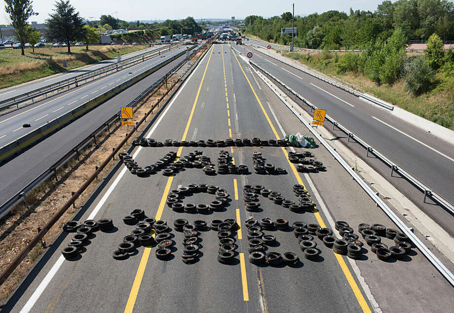 """Farmers use tires to write a message to French Prime Minister Manuel Valls : """"Valls, We Are Waiting For You"""" on the highway between Paris and Lyon in Limonest near Lyon, central France, Thursday, July 23, 2015. Angry French farmers block the famed Mont Saint Michel causeway and highways leading to the Alps, hoping to get more government help for margins they say are being chipped way by cheap imports and pressure from grocery chains. Thursday's protests were a rejection of the government offer to back loans to the farmers and delay tax payments as part of a 600 million euro plan. (AP Photo/Vincent Dargent)"""
