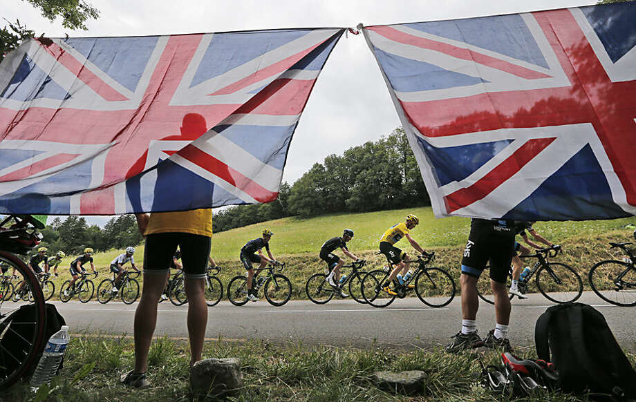 The pack with Britain's Chris Froome, wearing the overall leader's yellow jersey, passes spectators who attached the Union Jack flag to trees along the road during the eighteenth stage of the Tour de France cycling race over 186.5 kilometers (115.9 miles) with start in Gap and finish in Saint-Jean-de-Maurienne, France, Thursday, July 23, 2015. (AP Photo/Christophe Ena)