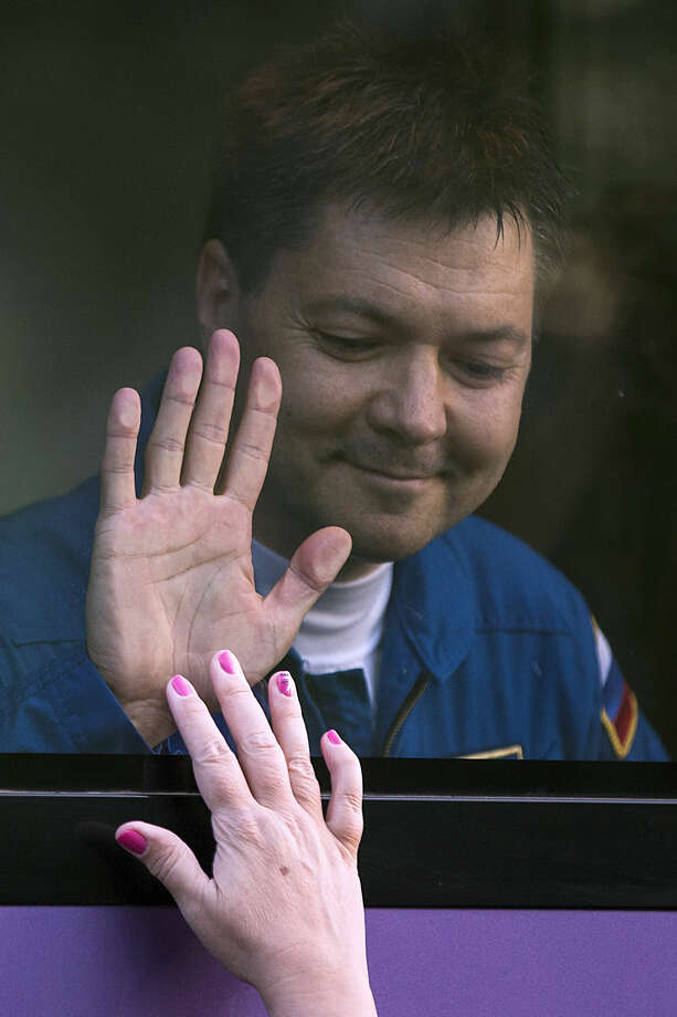 Russian cosmonaut Oleg Kononenko, a crew member of the next mission to the International Space Station, matches palm with his wife Tatiana out of a bus prior the launch of Soyuz-FG booster rocket with the space capsule Soyuz TMA-14M at the Russian leased Baikonur Cosmodrome, in Kazakhstan, Wednesday, July 22, 2015. (AP Photo/Pavel Golovkin)