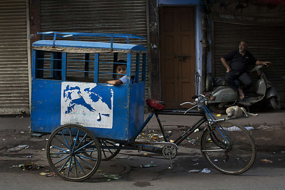 An Indian child on his way to school sits inside a custom-made cycle rickshaw as he awaits other children to join him in New Delhi, India, Wednesday, July 22, 2015. (AP Photo/Bernat Armangue)