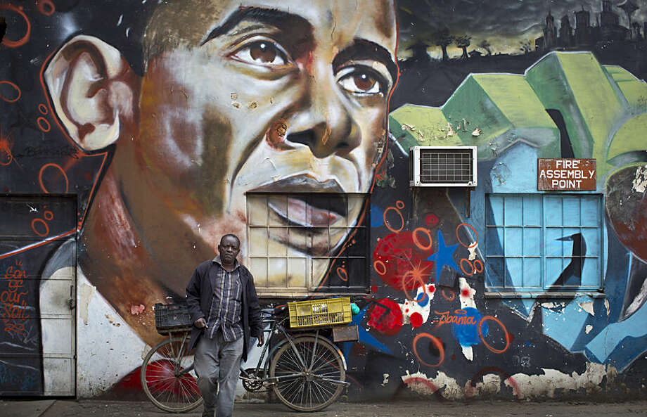 A man walks away after leaning his bicycle against a mural of President Barack Obama, created by the Kenyan graffiti artist Bankslave, at the GoDown Arts Centre in Nairobi, Kenya Wednesday, July 22, 2015. In his first trip to Kenya since he was a U.S. senator in 2006, Obama is scheduled to arrive in Kenya on Friday, the first stop on his two-nation African tour in which he will also visit Ethiopia. (AP Photo/Ben Curtis)