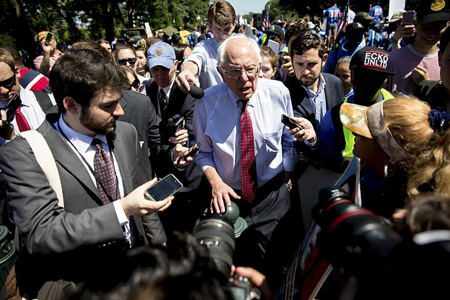 Democratic presidential candidate Sen. Bernie Sanders, I-Vt., speaks to reporters after speaking to federal contract workers at a rally on Capitol Hill in Washington, Wednesday, July 22, 2015, to push for a raise to the minimum wage to $15 an hour. (AP Photo/Andrew Harnik)