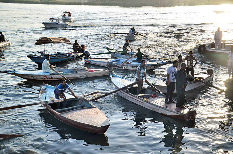 Egyptian volunteers look for victims of a passenger boat after it sunk in the river Nile in Giza, south of Cairo, Egypt, Thursday, July 23, 2015. Egypt's Interior ministry says more than a dozen civilians have drowned when a passenger boat traveling down the Nile near Cairo collided with a scow, causing the boat to capsize. (AP Photo/Samer Abdullah)