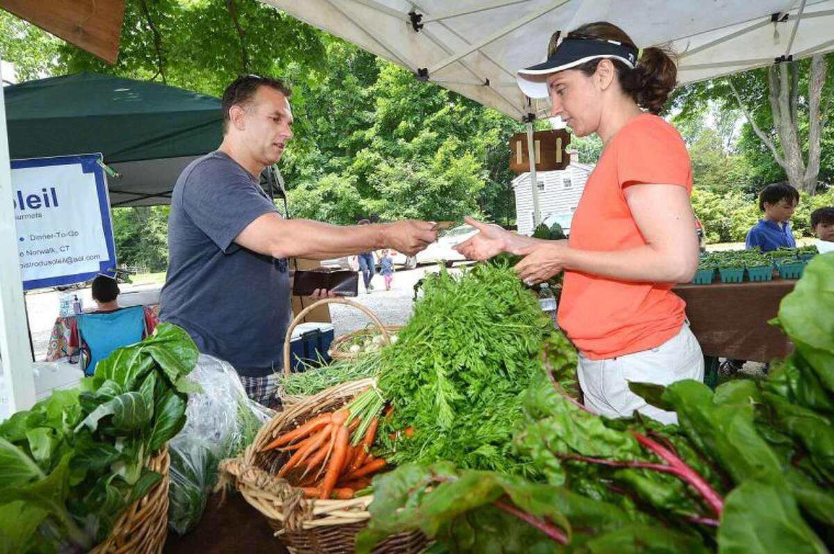 At Wilton's Farmers Market, Steve Simmons buys all the ingredients so he can prepare a gourmet dinner for his family, including garlic scapes, which he will sauté in a little butter and olive oil then add some parmesan cheese.
