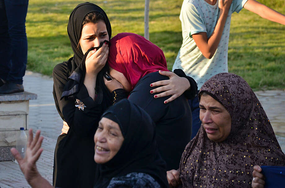 Egyptian women mourn for victims of a passenger boat after it sunk in the river Nile in Giza, south of Cairo, Egypt, Thursday, July 23, 2015. Egypt's Interior ministry says more than a dozen civilians have drowned when the passenger boat traveling down the Nile near Cairo collided with a scow, causing the boat to capsize. (AP Photo/Samer Abdullah)