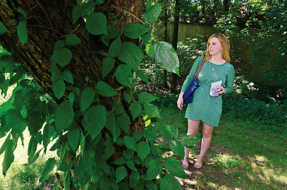 Hour photo / Erik Trautmann Hour reporter Robin Sattler hides herself at the Mathews Park as part of the Norwalk police demonstration of how their new tracking device, Project Lifesaver, works Thursday.