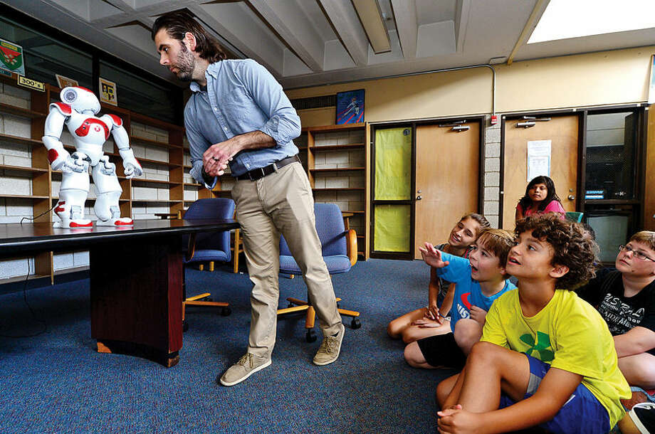 Hour photo / Erik Trautmann Norwalk Public Schools Personal Fulfillment (PF) Campers listen as Manager of digital experience at the Westport Library, Alex Giannini demonstrates, two NAO humanoid robots, Vincent and Nancy, during a visit to Norwalk High School Thursday afternoon.
