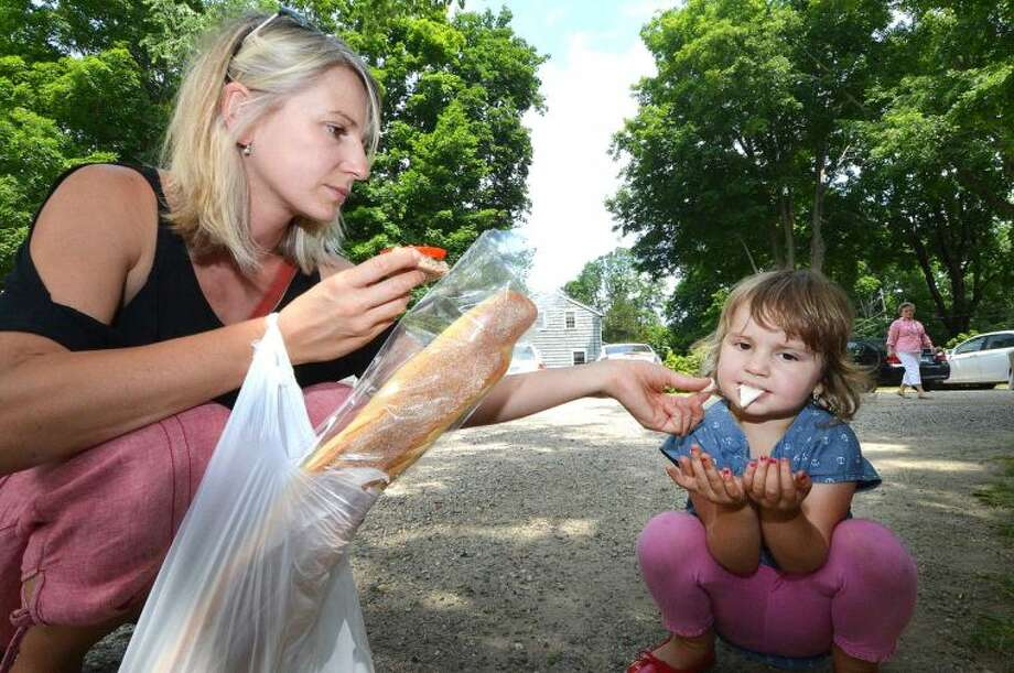 Amelia Hamilton, 3 years old, enjoys a free sample of fresh-made mozzarella from mom, Gabriela, compliments of the brothers Castano at Beldotti Bakery from Stamford at Wilton Farmers Market.