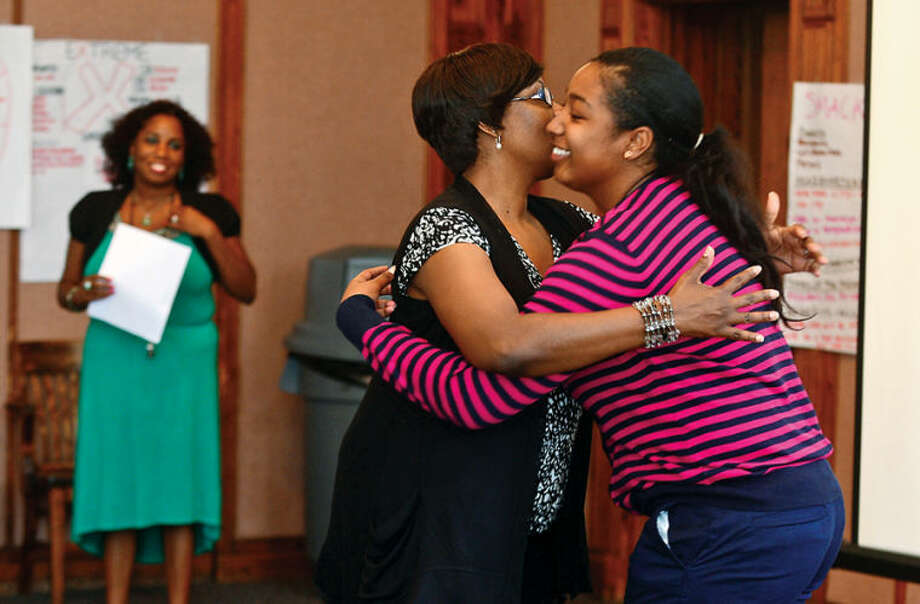 Hour photo / Erik Trautmann Graduate Imani Hardie thanks program coordinator Darlene Young during the graduation ceremony for the paricipants in the Mayor's Summer Youth Employment Program Friday at City Hall.