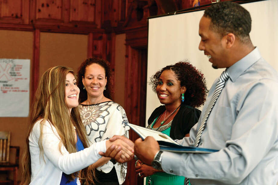 Hour photo / Erik Trautmann Melanie Hernandez receives her certificate STRIVE staff from Don Williams, Dawn-Marie Williams and Matilda Bonilla during the graduation ceremony for the paricipants in the Mayor's Summer Youth Employment Program Friday at City Hall.