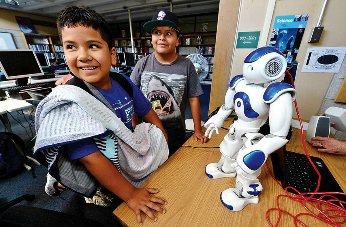 Hour photo / Erik Trautmann Norwalk Public Schools Personal Fulfillment (PF) Campers, Frank Escalante and George Diaz, both 10, watch a demonstration of the Westport Library's NAO humanoid robot, Vincent, during a visit to Norwalk High School byy the library's digital experience team Thursday afternoon.