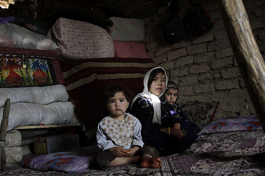 Afghan internally displaced children pose for a photograph at their makeshift home on the outskirts of Herat province, Kabul, western Afghanistan, Wednesday, July 22, 2015. (AP Photo/Hoshang Hashimi)