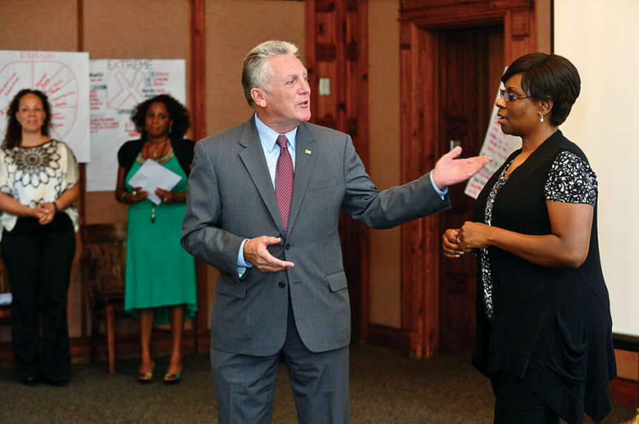 Hour photo / Erik Trautmann Norwalk Mayor Harry Rilling thnaks program coordinator Darlene Young during the graduation ceremony for the paricipants in the Mayor's Summer Youth Employment Program Friday at City Hall.