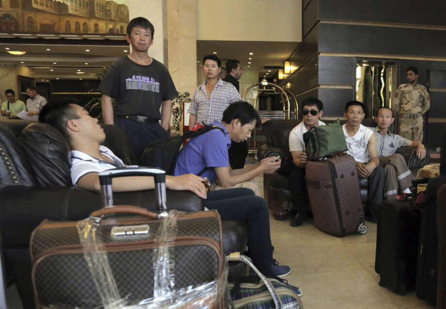 Chinese workers who fled from Samarra, Iraq, wait for buses to begin their journey home as they sit at a hotel in Baghdad, Iraq, Saturday, June 28, 2014. China's official Xinhua news agency said that more than 1,200 Chinese workers who had been trapped in the embattled northern Iraqi city of Samarra have been evacuated safely to Baghdad, with the Iraqi military providing security. (AP Photo/Khalid Mohammed)